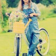 Spring cycling - girl with flowers riding a bike — Stock Photo #47335993