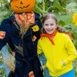 Halloween, Scarecrow and happy girl  in the garden — Stock Photo #47336593