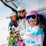 Ski lift, skiing, ski resort - happy skiers on ski lift — Stock Photo #47437029