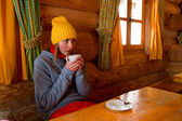 Apres ski, winter holiday - young snowboarder girl resting in mountain hut — Stock Photo