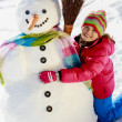 Winter fun, happy kid playing with snowman — Stock Photo