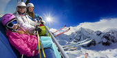 Ski lift, skiing, ski resort - happy skiers on ski lift — Stock Photo