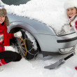 Winter, travel - woman putting snow chains onto tyre of car — Stock Photo #47812715