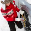 Winter, travel - woman putting snow chains onto tyre of car — Stock Photo