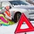 Winter, travel - woman putting snow chains onto tyre of car — Stock Photo #47813181