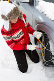 Winter, travel - woman putting snow chains onto tyre of car — Stockfoto