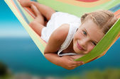 Summer vacation - lovely girl in colorful hammock — Stock Photo