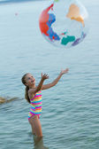Summer game, young girl playing in the sea — Stock Photo