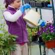 Gardening, planting concept - lovely girl watering flowers in the greenhouse — Stock Photo #47933135