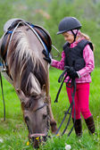 Horse and jockey - little girl is grazing the horse on the meadow — Stock Photo