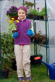 Gardening, planting - lovely girl with flowers seedling in the greenhouse — Stock Photo
