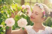 Rose garden - beautiful girl playing in the rose garden — Stock Photo