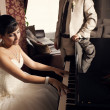Young beautiful bride playing the grand piano — Stock Photo