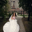 Happy bride in summer park on background palace — Stock Photo