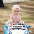 Smiling little girl steers electromobile — Stock Photo
