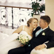 Foto Stock: Wedding couple hugging, bride and groom on sofa