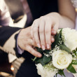 A newly wed couple place their hands on a wedding bouquet  — Zdjęcie stockowe