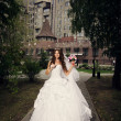 Happy bride in summer park on background palace — Stock Photo #26613489