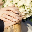 Hands of bride and groom with bouquet of flowers — Stock Photo