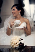 Beautiful bouquet and beautiful bride on the background — Stock Photo