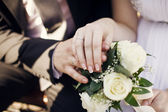 A newly wed couple place their hands on a wedding bouquet — Stock Photo