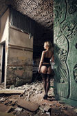 Beautifull woman in underwear standing near wall in old house — Stock Photo