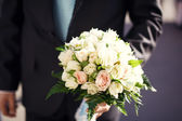 A young groom holding bouquet of flowers — Stock Photo