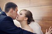 Bride and groon kissing on wooden background — Stock Photo