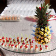 Pineapple and strawberries on skewers — Stock Photo