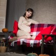 Stock Photo: Young pregnant woman sitting on sofa
