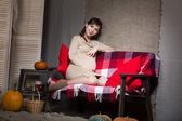 Young pregnant woman sitting on sofa — Stok fotoğraf