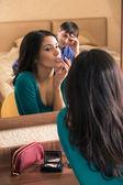 Beautiful woman putting make up — Stock Photo