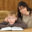 Beautiful happy Caucasian mother with her son reading a book — Stock Photo