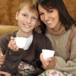 Beautiful mom and child sitting on the couch with a cup — Foto Stock
