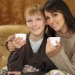 A Caucasian mother with her son sitting on the couch — Stock Photo