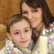 A beautiful mother with her son sitting on the couch — Стоковая фотография