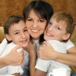 Beautiful mother and sons sitting — Stock Photo