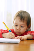 Nice Caucasian young girl sits drawing — Stock Photo
