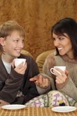 Beautiful mother and child sitting on the couch with a cup — Stock Photo