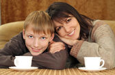 Beautiful mama and son sitting on the couch with a cup — Stock Photo