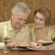 Beautiful Caucasian elderly couple sitting at a table — Stock Photo