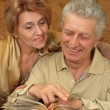 Beautiful happy elderly couple sitting at a table — Stock Photo