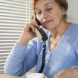 Beautiful Caucasian aged female with a cup and a telephone — Stock Photo