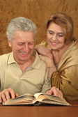 Caucasian elderly couple sitting at a table — Stock Photo