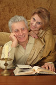 Beautiful pretty elderly couple sitting at a table — Stock Photo
