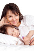 A beautiful good Caucasian mother with her daughter lying — Stock Photo