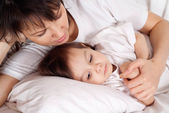 A beautiful Caucasian mummy with her daughter lying with a penci — Stock Photo