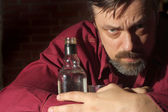Caucasian adult man with a nice bottle sitting — Stock Photo