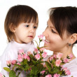 Beautiful woman with a daughter and flowers — Stock Photo #12842284