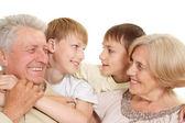 Grand-père et grand-mère avec leurs petits-enfants intéressants — Photo